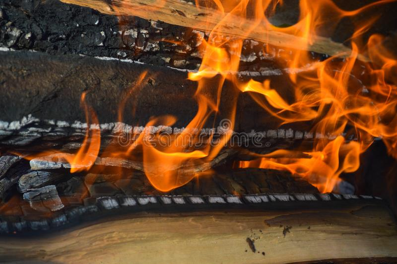 Los tablones carbonizados calientes ardientes de madera de la madera abren una sesión un fuego con las lenguas del fuego y del hu imágenes de archivo libres de regalías