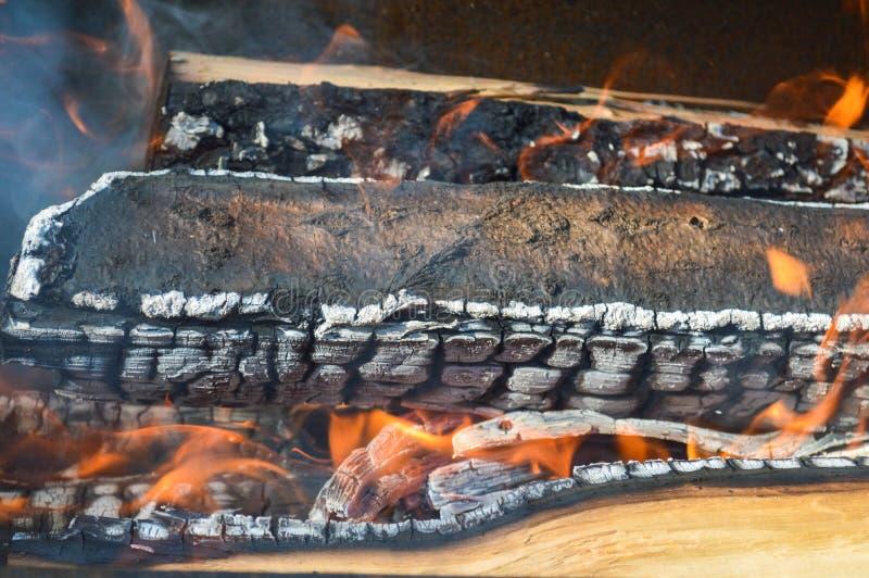 Los tablones carbonizados calientes ardientes de madera de la madera abren una sesión un fuego con las lenguas del fuego y del hu foto de archivo libre de regalías