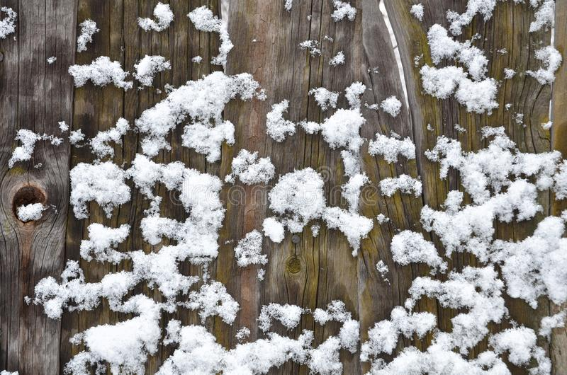 Los tablones viejos se cubren con los terrones de la nieve fotos de archivo libres de regalías