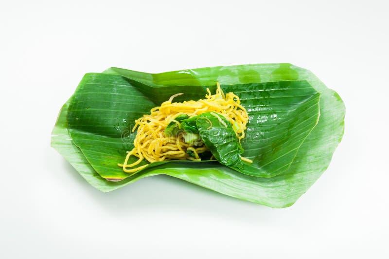 Los tallarines amarillos secos fritos en un plátano hojean en el fondo blanco imagen de archivo libre de regalías