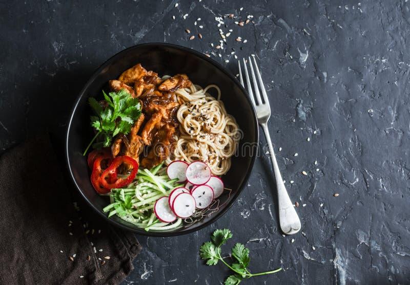 Los tallarines de arroz y el pollo del teriyaki sofríen con los pepinos y los rábanos conservados en vinagre rápidos En un fondo  fotos de archivo