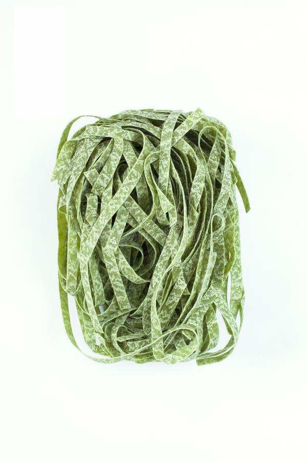 Los tallarines secos de la espinaca de las pastas, sola jerarquía del fettuccine aislaron o fotos de archivo