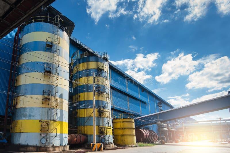 Los tanques de agua industriales Los tanques de acero al aire libre del almacenamiento en montón con la opinión de cielo azul imagen de archivo