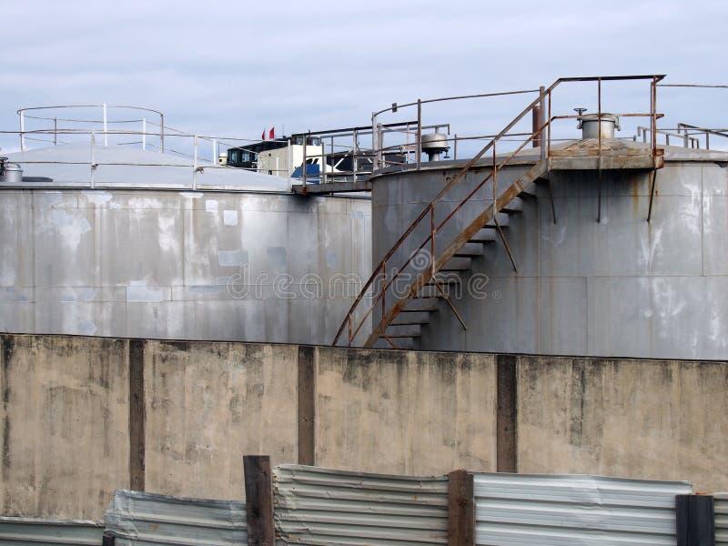 Los tanques de almacenamiento industriales de acero con las escaleras y las calzadas oxidadas detrás de una cerca lamentable y de imagen de archivo