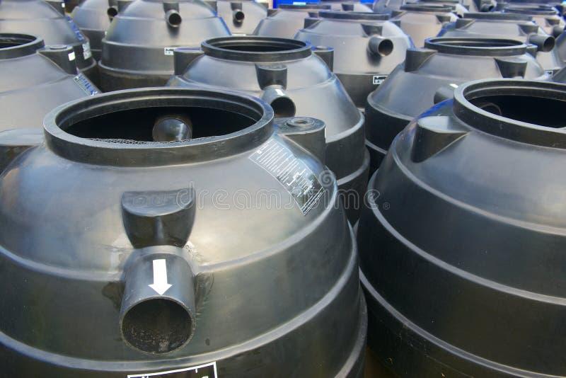 Los tanques de almacenamiento plásticos negros del agua imagenes de archivo