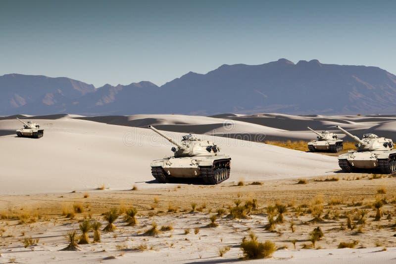 Los tanques de ejército maniobran en la arena blanca del desierto fotografía de archivo libre de regalías