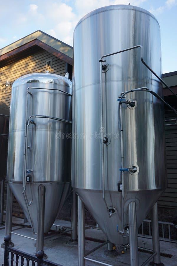 Los tanques de la elaboración de la cerveza de acero inoxidable y de almacenamiento en una cervecería foto de archivo