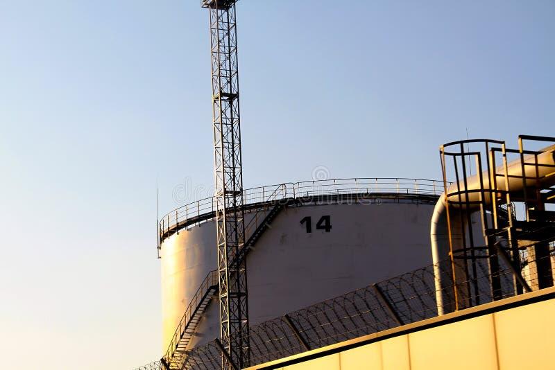 Los tanques industriales blancos grandes para el producto petroquímico o aceite o combustible en el puerto de cargamento del acei fotografía de archivo libre de regalías