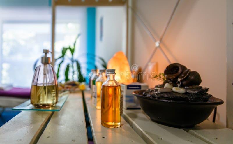 Los tarros con lociones y las esencias en una tabla en una terapia se centran foto de archivo