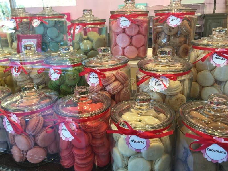 Los tarros de los macarrones coloridos se apelmazan en la exhibición en frente de la tienda imagen de archivo libre de regalías