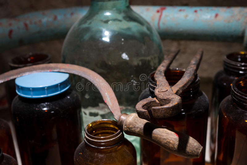 Los tarros, la hoz y las pinzas de cristal con sangre salpicaron la pared en staine imagen de archivo libre de regalías