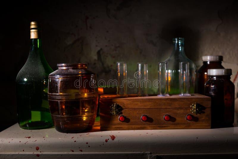 Los tarros y las botellas de cristal con sangre salpicaron la pared foto de archivo