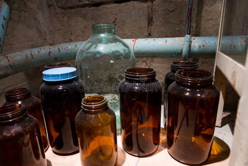 Los tarros y las botellas de cristal con sangre salpicaron la pared en labo manchado fotos de archivo libres de regalías