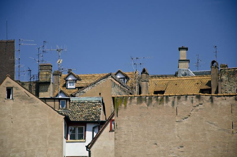 Los tejados con los áticos, las tablas rojas y las antenas en fondo del cielo azul imagen de archivo libre de regalías