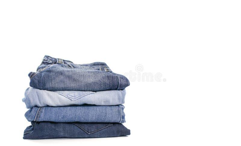 Los tejanos del dril de algodón apilan en el fondo blanco Ropa, moda, caridad foto de archivo libre de regalías