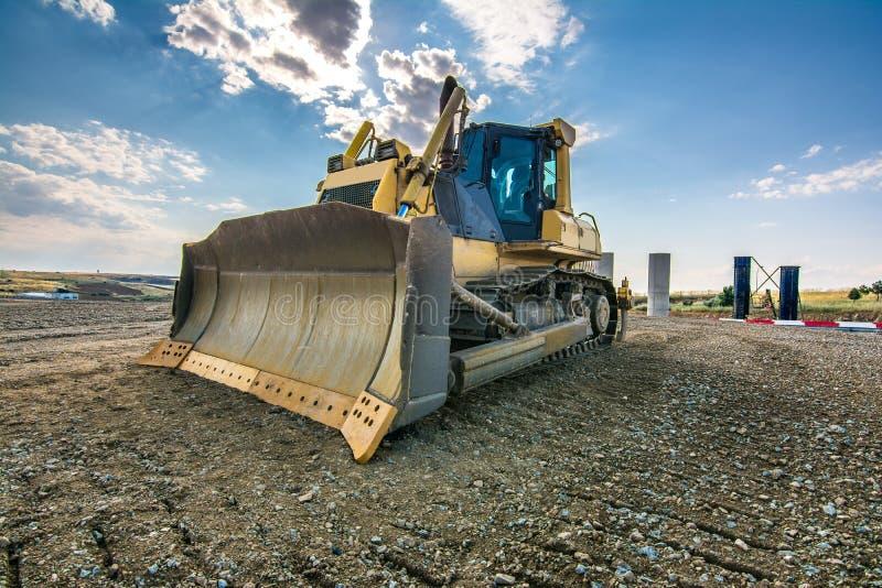 Los terraplénes de ejecución del excavador trabajan en los trabajos de la extensión de la carretera de Madrid-Segovia-Valladolid imagen de archivo