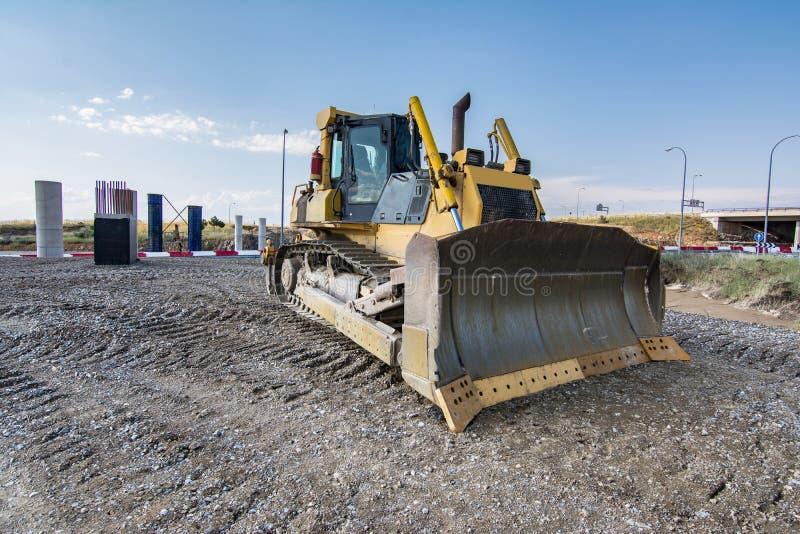 Los terraplénes de ejecución del excavador trabajan en los trabajos de la extensión de la carretera de Madrid-Segovia-Valladolid fotografía de archivo libre de regalías