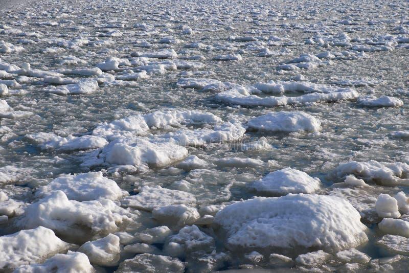 Los terrones del frazil de la nieve y del hielo en la superficie de la congelación rive foto de archivo