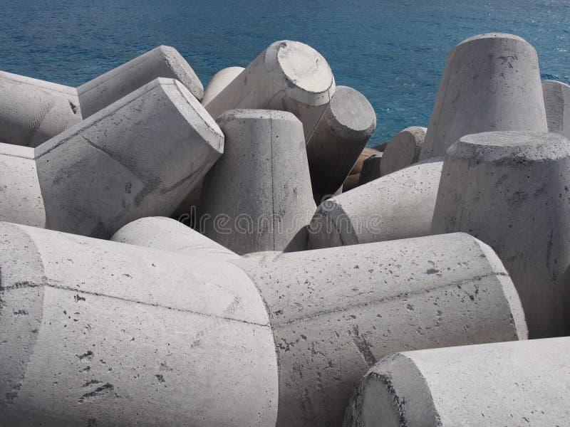 Los tetrapods concretos prevenían la erosión costera en montones que entrelazaban delante de un mar azul brillante imagenes de archivo