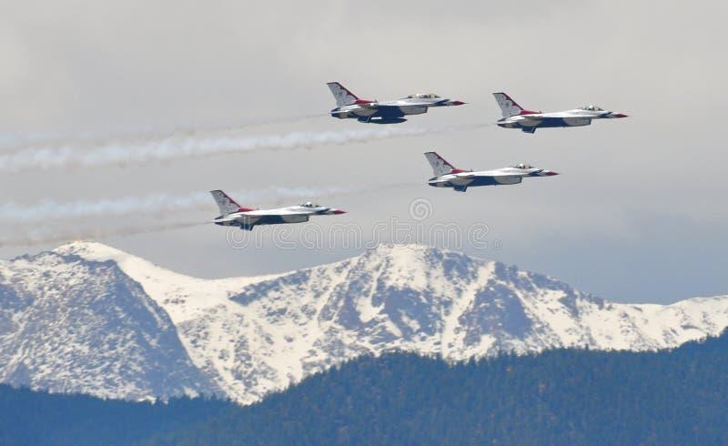 Los Thunderbirds de la fuerza aérea vuelan sobre rocoso capsulada nieve imagen de archivo