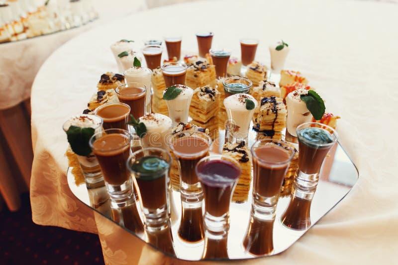 Los tiros sabrosos deliciosos del chocolate en vidrios y tortas deliciosas se cierran imágenes de archivo libres de regalías
