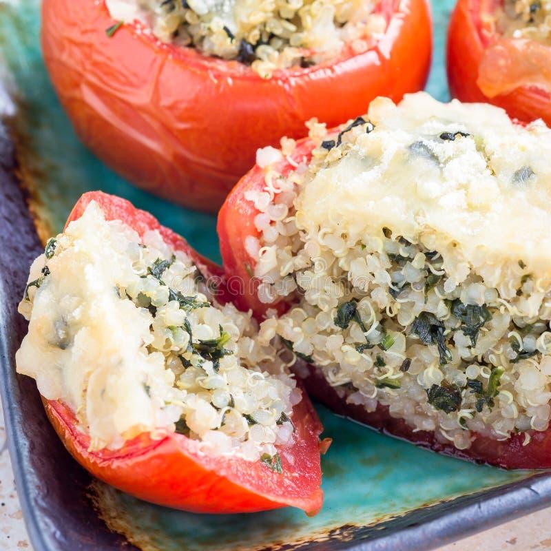 Los tomates cocidos rellenos con la quinoa y la espinaca remataron con queso derretido en de cerámica una placa, formato cuadrado foto de archivo libre de regalías