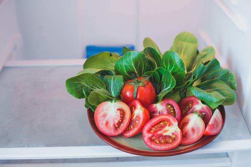 Los tomates cortaron en mitad y la col de Bok Choy Chinese en una placa I imágenes de archivo libres de regalías