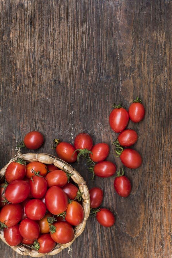 Los tomates de cereza, son los pequeños tomates en el top y la armadura de cesta de madera fotos de archivo