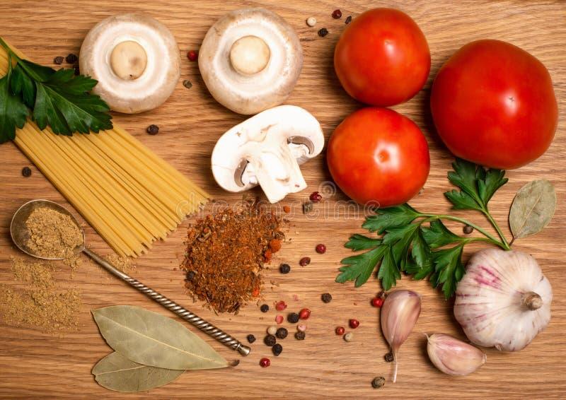 Los tomates de los espaguetis proliferan rápidamente con las hierbas en un viejo y un vintage wo imagen de archivo libre de regalías