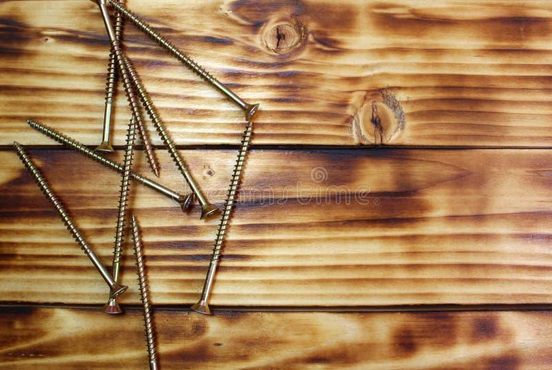 Los tornillos largos del hierro mienten en una pila en una tabla de madera fotos de archivo