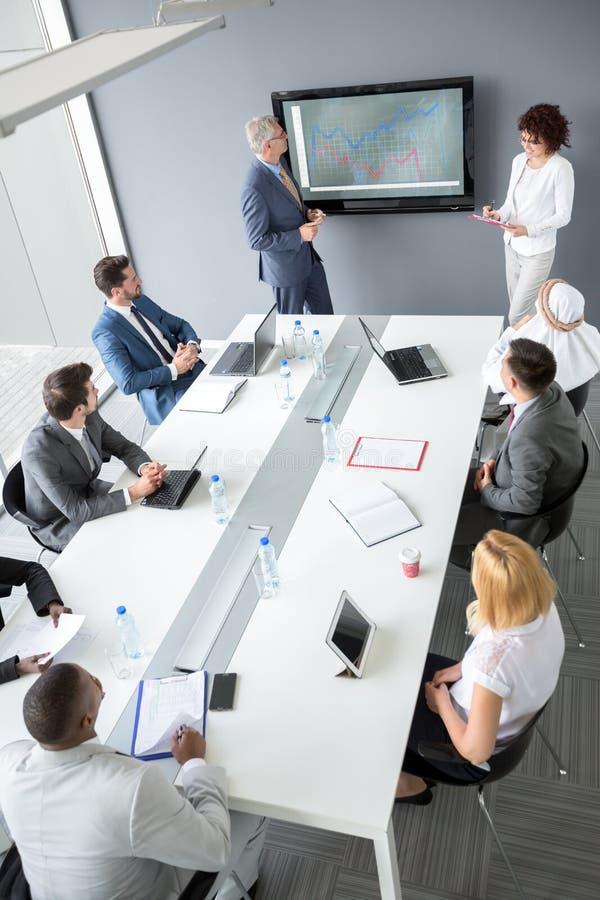 Los trabajadores agrupan en la mesa de reuniones escuchan encargado fotos de archivo