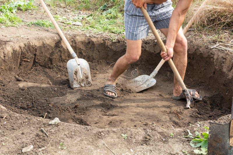 Los trabajadores cavan un hoyo para un tanque séptico foto de archivo libre de regalías