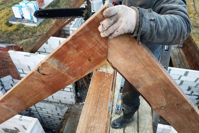 Los trabajadores cortaron los vigas en el tejado de la casa de la motosierra imagenes de archivo