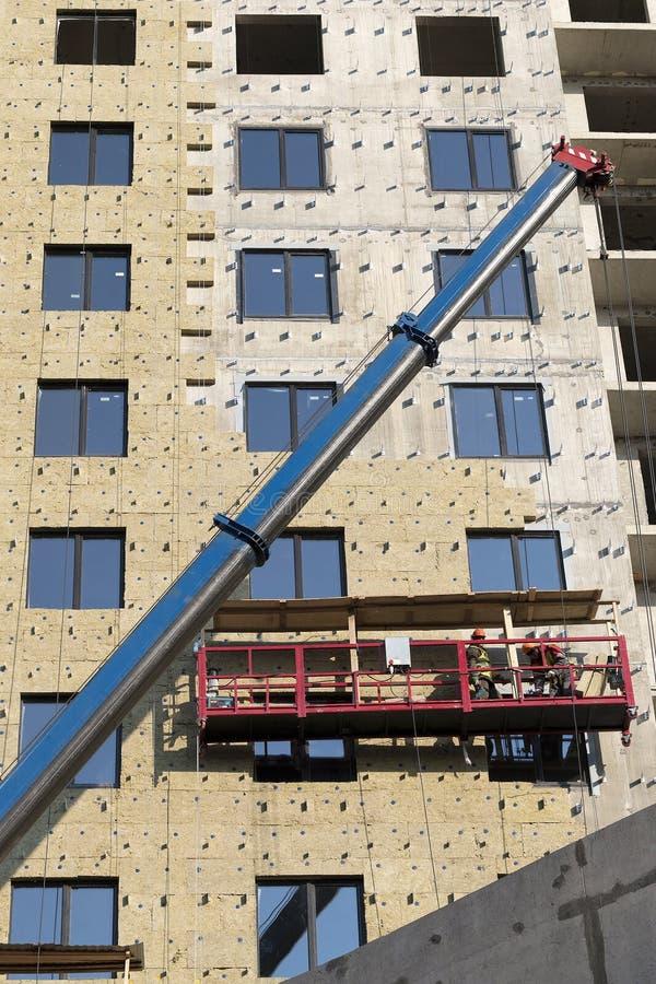 Los trabajadores de construcci?n cubren la nueva pared constructiva con una capa de aislamiento de las lanas de cristal foto de archivo libre de regalías