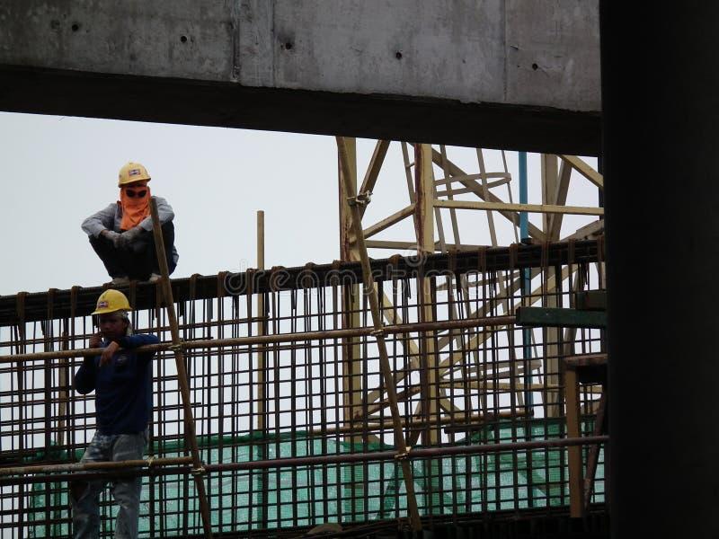 Los trabajadores de construcción están instalando las barras de acero en acero del hormigón del sitio de la tensión de los posts  foto de archivo