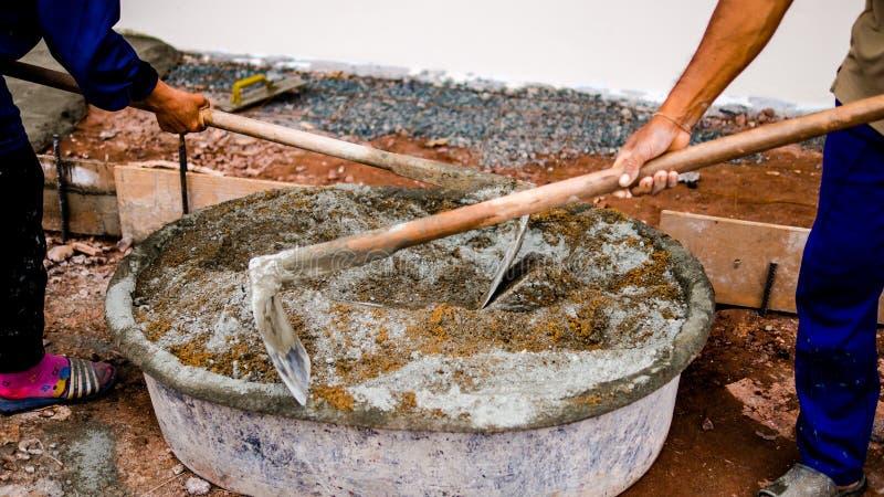 Los trabajadores de construcción están mezclando el cemento y la arena concretos imagenes de archivo