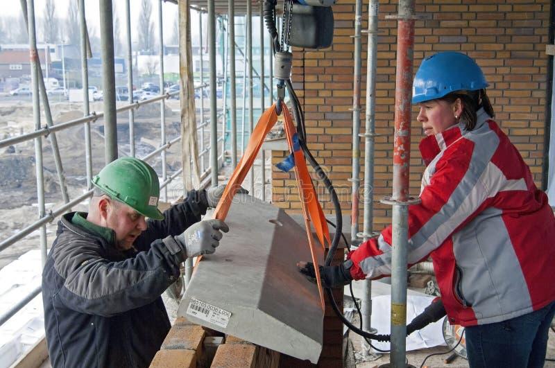 Los trabajadores de construcción de sexo femenino y de sexo masculino trabajan juntos imagen de archivo