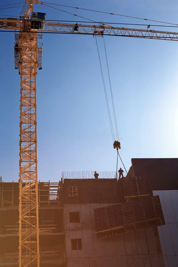 Los trabajadores de los constructores instalan una placa para el hormigón de colada con un hig imagen de archivo