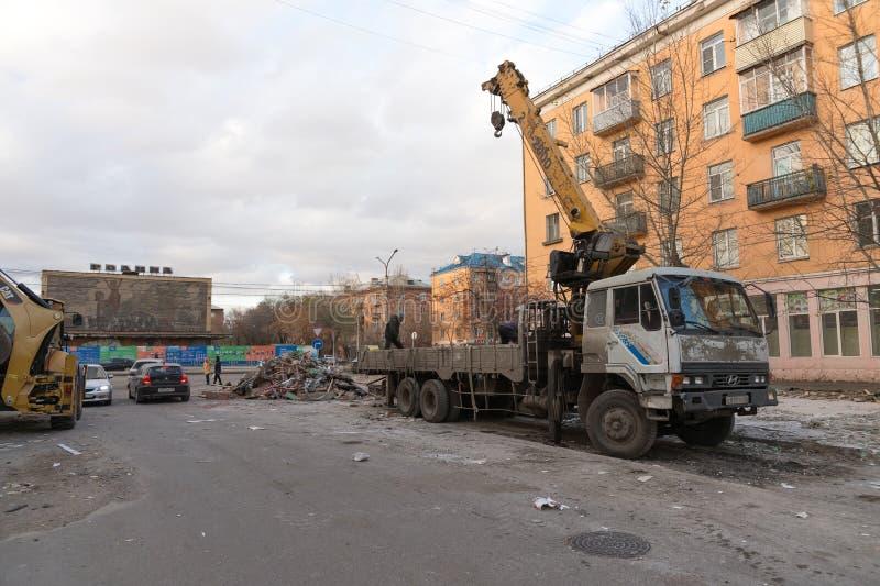 Los trabajadores de servicios públicos pusieron la basura de la construcción de la demolición de pabellones viejos en un camión c foto de archivo libre de regalías