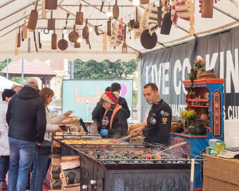 Los trabajadores de un café de los alimentos de preparación rápida de la calle sirven a clientes en la ciudad de Sibiu en Rumania fotos de archivo