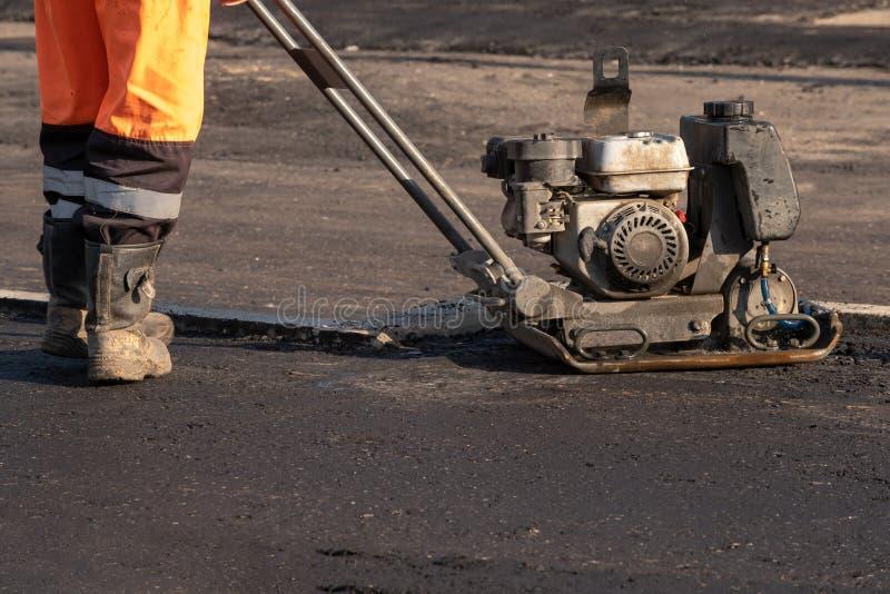 Los trabajadores del camino condensan el asfalto con un pisón vibrante en el camino Trabajador con el compresor en un sitio de la fotos de archivo libres de regalías
