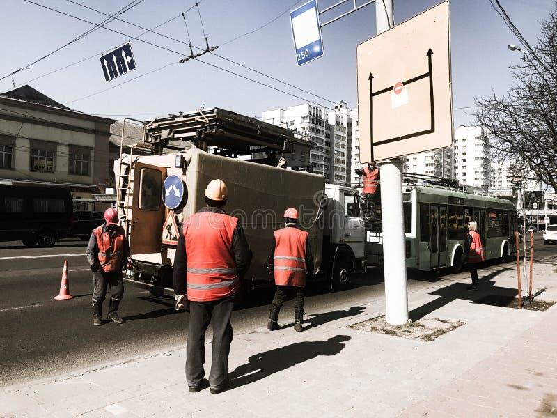Los trabajadores del camino en trajes, guardapolvos y cascos de la construcción trabajan en la reparación del camino en la calle, foto de archivo