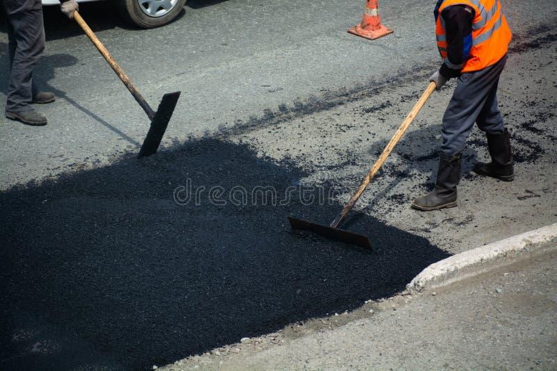 Los trabajadores del camino están pavimentando fotos de archivo