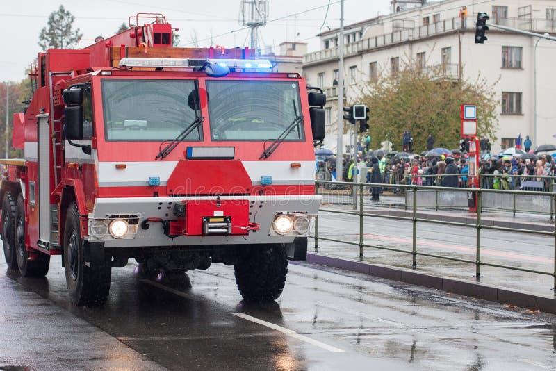 Los trabajadores del departamento de bomberos est?n montando la gr?a del coche de bomberos en desfile militar imagen de archivo libre de regalías