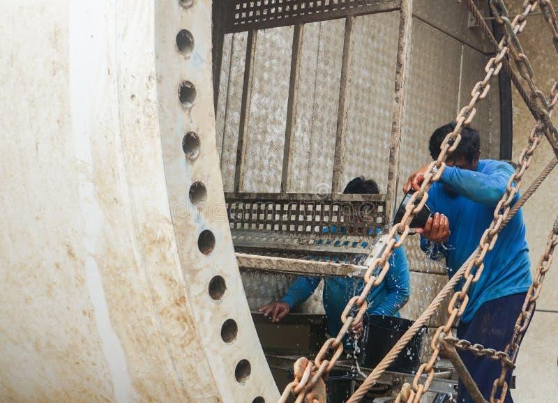 Los trabajadores en uniforme del azul limpian la torre de la turbina de viento antes de la instalación foto de archivo libre de regalías