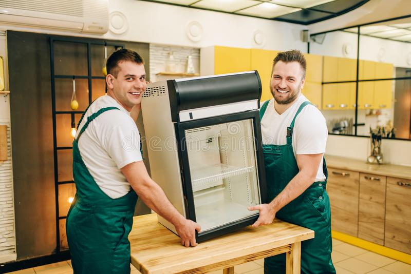 Los trabajadores en uniforme instalan el refrigerador en casa imágenes de archivo libres de regalías