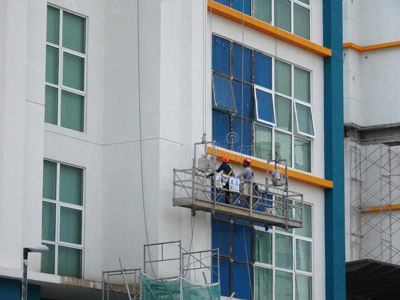 Los trabajadores están en curso de exterior de la limpieza y del mantenimiento el edificio usando una góndola del servicio imagen de archivo libre de regalías
