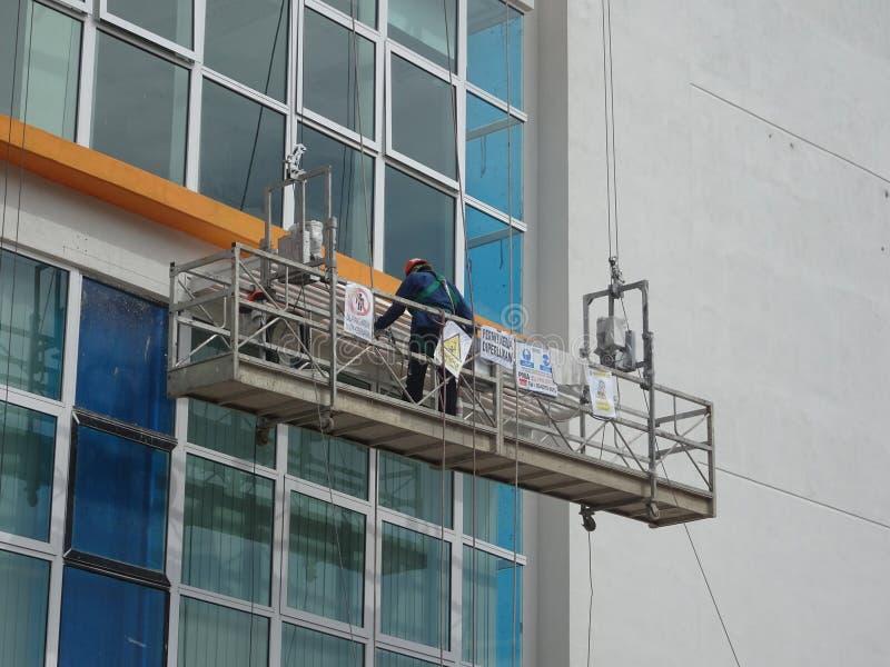 Los trabajadores están en curso de exterior de la limpieza y del mantenimiento el edificio usando una góndola del servicio imágenes de archivo libres de regalías