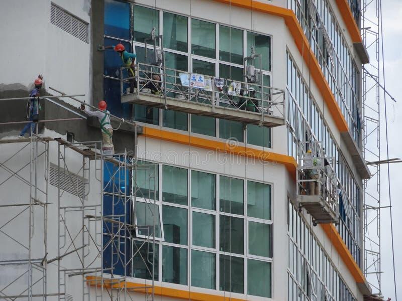 Los trabajadores están en curso de exterior de la limpieza y del mantenimiento el edificio usando una góndola del servicio fotografía de archivo libre de regalías