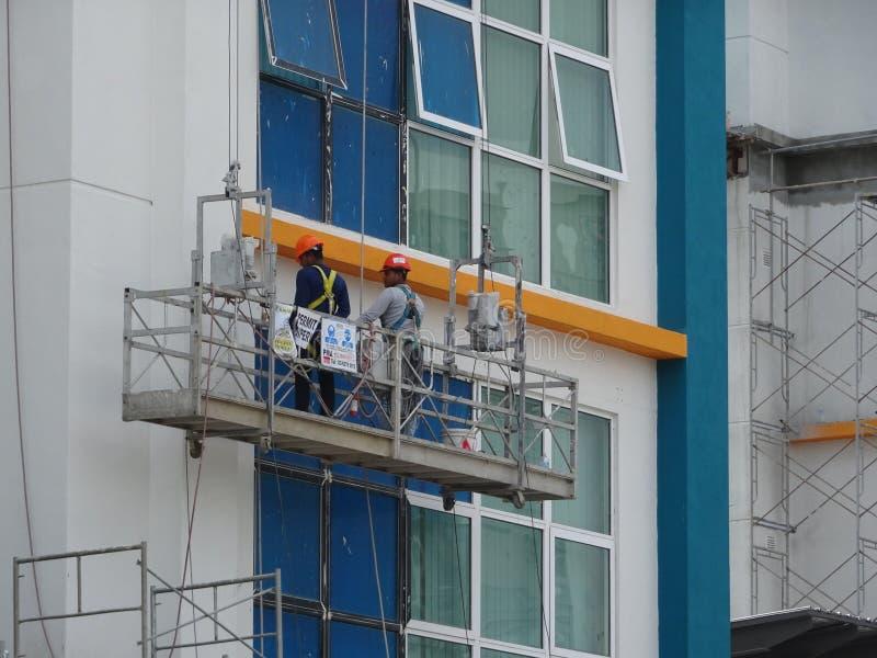Los trabajadores están en curso de exterior de la limpieza y del mantenimiento el edificio usando una góndola del servicio fotografía de archivo